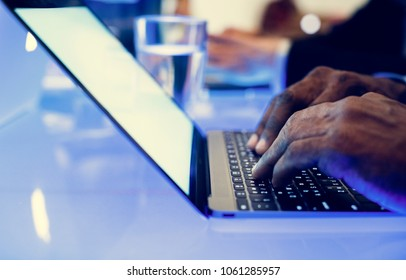 Hand on a laptop working at cyber space table