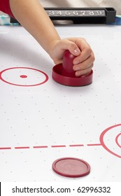 Hand on a mallet over air hockey table