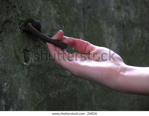 hand on an old horse hitching ring on a historical wall