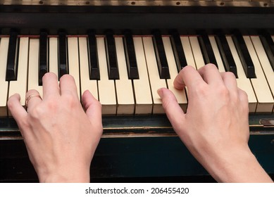 The hand on old piano keyboard