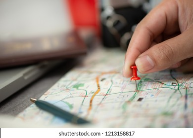 Hand on pointing red pin plan to travel on map, Travel concept