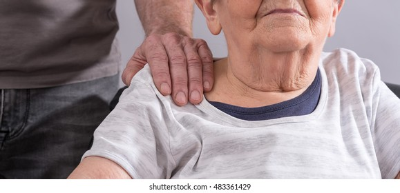 Hand on shoulder of an old woman
