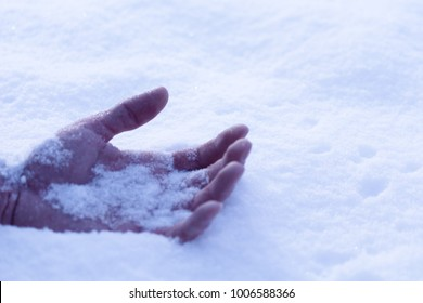 a hand on the snow, a symbol of a frozen man who died from the cold concept, close up, selective focus, copy space