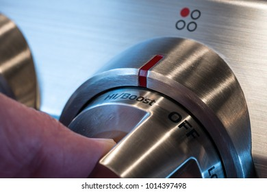 Hand on stainless steel control knob on induction cooktop or hob set to High or boost power