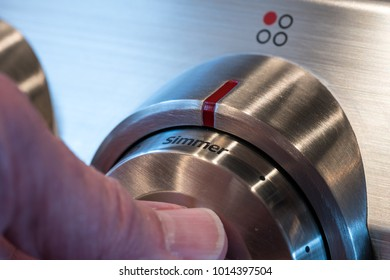 Hand on stainless steel control knob on induction cooktop or hob set to simmer