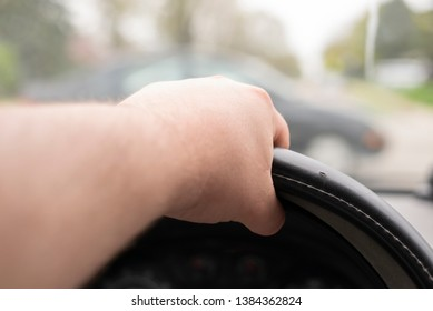 A hand on the steering wheel of a car.