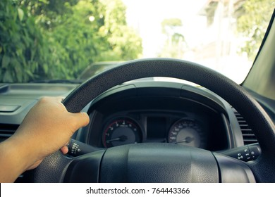 Hand on steering wheel while driving forward. Control of steering in the driving safety.