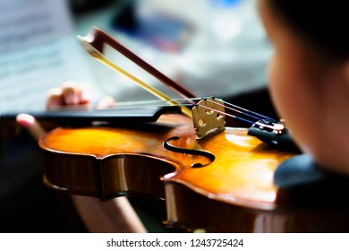 The girl's hand on the strings of a violin blurred - Close-up violin playing