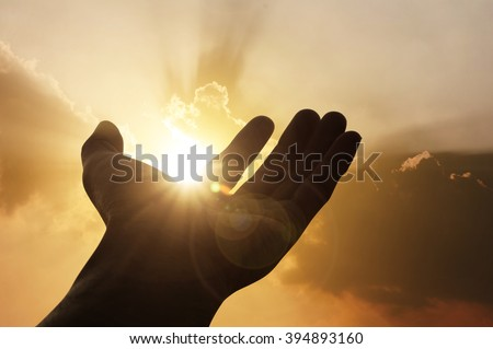 Hand on sunset background success, peace,freedom business concept