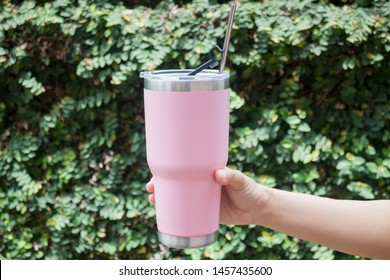 Hand on thermos tumbler mug with metal drinking straw, stock photo