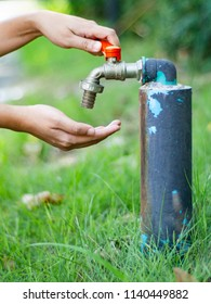 Hand on water tap with green grass background