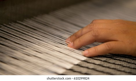 Hand on weaving,Weaving cloth for using in local village ,Woman working at the loom. Thailand national crafts. Focus on the fabric, classic asian loom at work, traditional thai loom detail