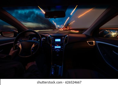 Hand on the wheel, one-handed operation. The car moves at a fast speed in the night of snooker. Blurred road with lights with a car at high speed