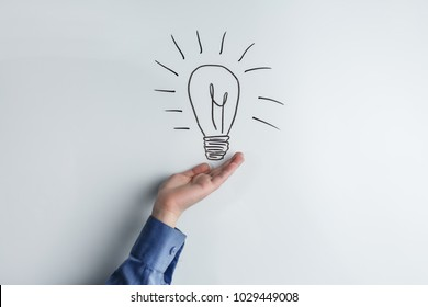 hand on white board background with painted bulb, concept of creative idea