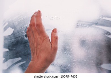 Hand on window, waiting and looking, condensation on window, drops, winter time, melancholy and sad mood,