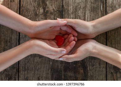 hand in hand on wooden background, heart in hands