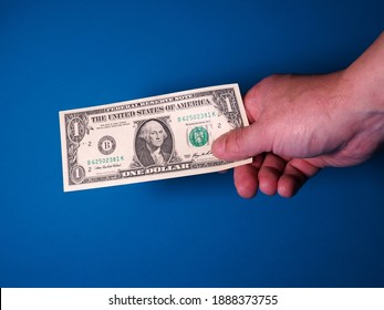 Hand with one dollar isolated on a blue background