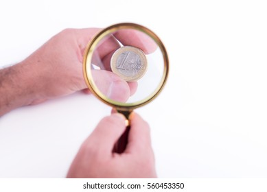 Hand with a one euro coin magnified by a magnifying glass on white background