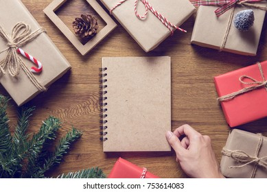 Hand Open book with Christmas gift box and tree branch decor on wooden table background. Flat lay, Top view with copy space