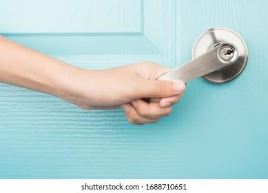 Hand open door knob blue background