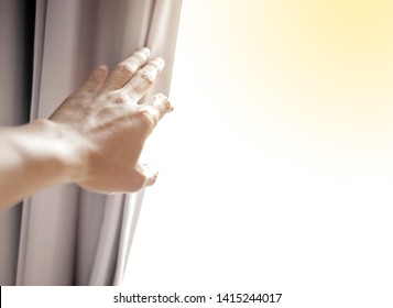 Hand open the white curtain and Looking through the window glass outside in the morning ,Curtain interior decoration in living room, hope concept