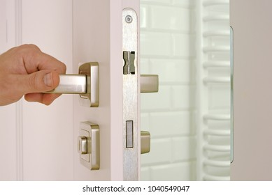 Hand open the white door to the bathroom