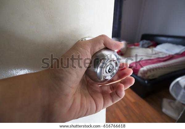 A hand opening bedroom's door.