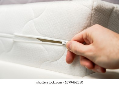 Hand opening cover of new mattress with zipper. Changing and washing cover. Front view. Close up