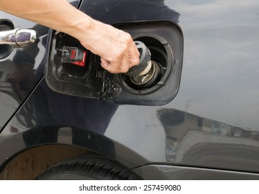 Hand opening the oil filler cap