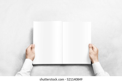 Hand opening white journal with blank pages mockup. Arm in shirt holding clear magazine template mock up. Man reading double-pages book first person view. Mag layout spread.
