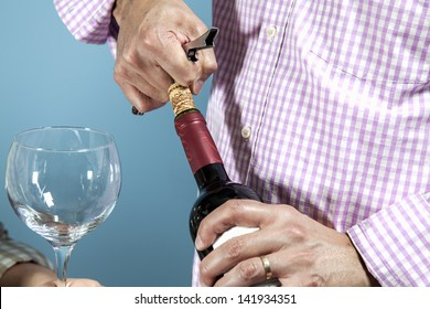 hand opening a wine bottle with a corkscrew between a wineglass / A man uncorking a bottle of red wine