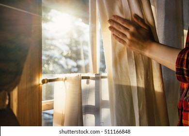 Hand Opens Curtain on the Wooden Cottage House Window. Bright Sunlight Shines Through. Beautiful snowy Winter morning light behind the Chalet Window.
