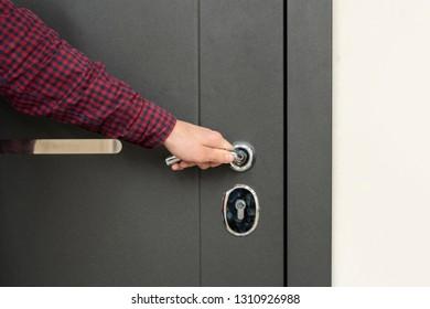 hand opens the door to the apartament