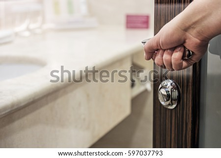 Hand opens the door to the bathroom at the hotel
