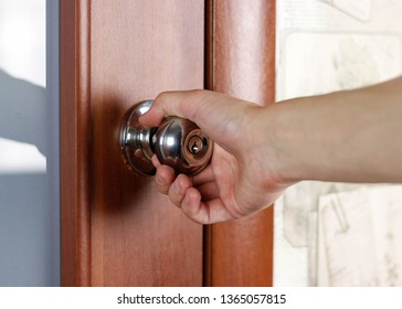 Hand opens the door by the handle. Close up.