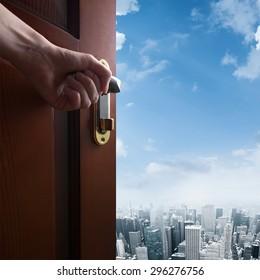 hand opens door to the city downtown