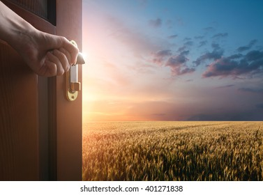 hand opens the door to the meadow with green grass and glue sky