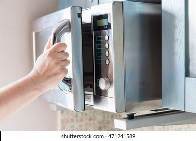 hand opens door of microwave oven for heating food