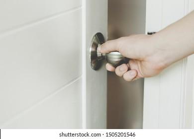 hand opens empty room door to freedom. men hand close door knob or opening the door, grand opening.