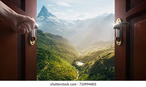 hand opens empty room door to nature and mountains - Shutterstock ID 710994403