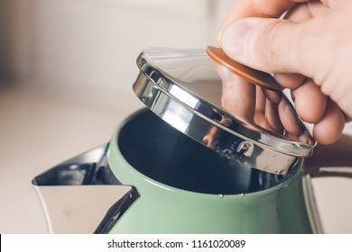 The hand opens the lid of the electric kettle