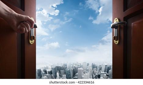 hand opens room door to the city
