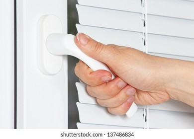 Hand opens the white plastic the window with jalousie