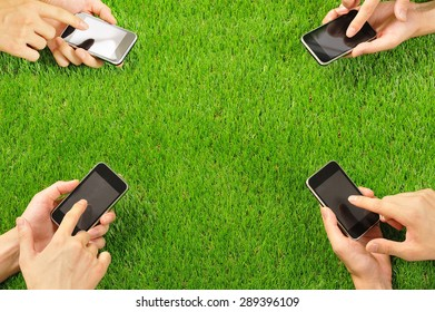 Hand to operate the smart phone,green grass