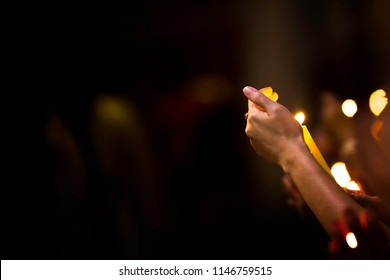 Hand and orange candles. To prevent the wind from blowing the candle out. Candles to indicate gratitude to the benefactor.