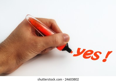 Hand and orange pen writing the word yes on white paper