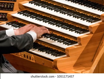 Hand of organist playing on organ