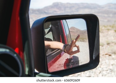 Hand out a side mirror of a red vehicle.