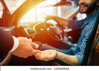 Hand over of car keys. Handsome Young bearded man in casual wear buying a car in dealership.