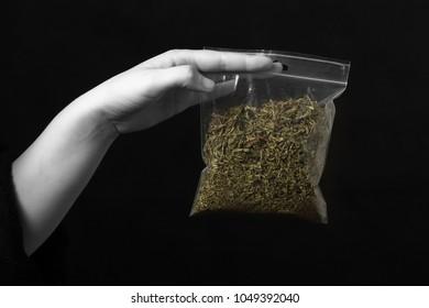 hand with pack of marijuana on black background